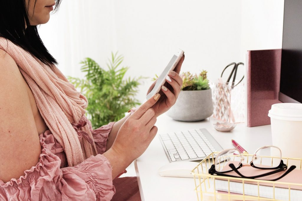 A woman in pink holding a phone - Pinterest Management header photo