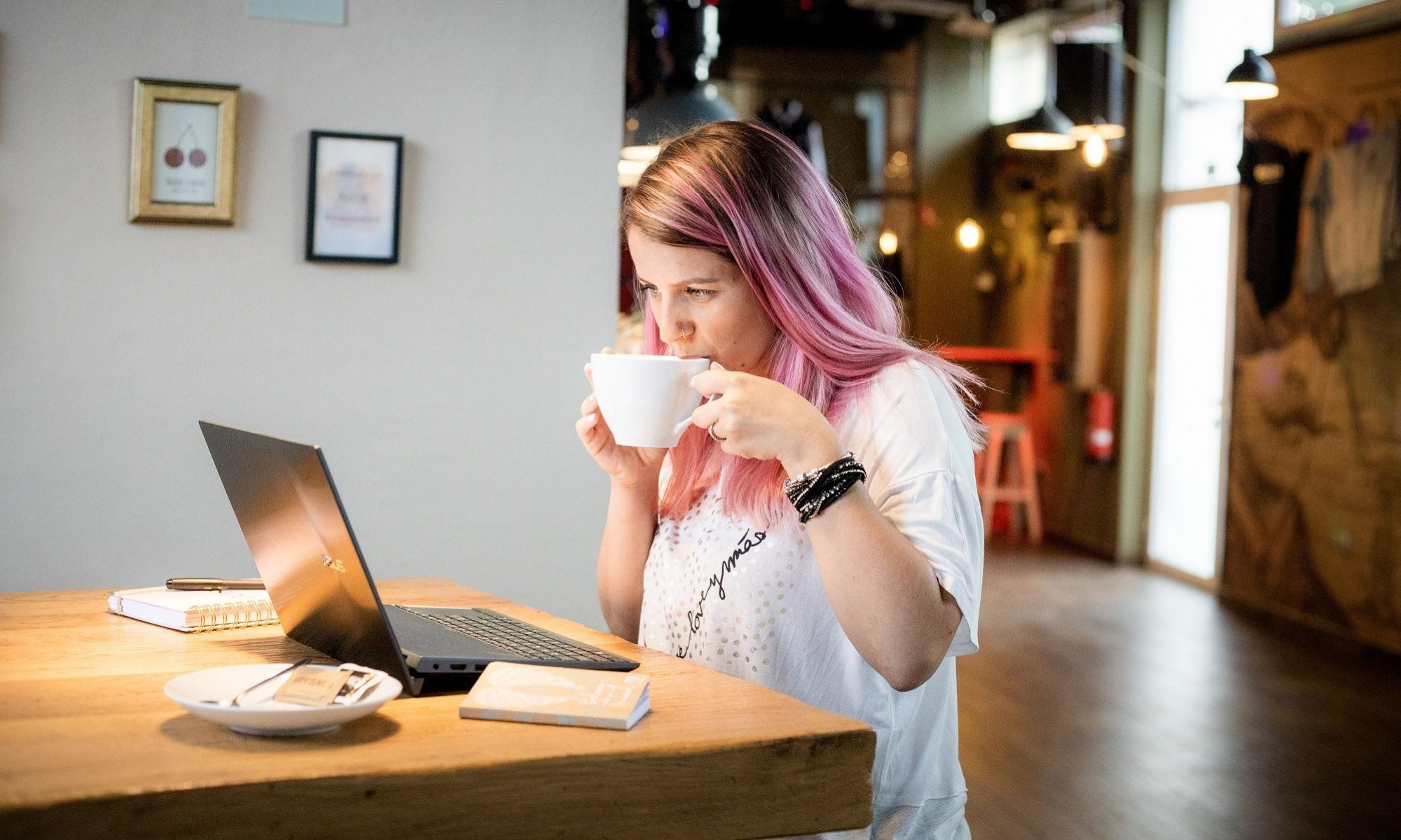 Sandra S. Media blog - a woman sitting in a coffee shop with laptop and drinking coffee